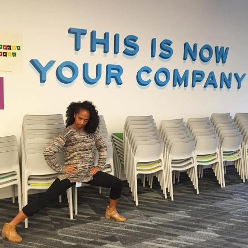 "A filipino american woman in tech on her first day at a tech company, lunging in front of a poster that says ""This Is Your Company Now."" This woman quit her job to travel two years later."