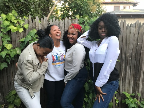 Four women of color in tech laughing in front of a fence at a backyard party, showing that representation means having every type of face present in influential spaces.