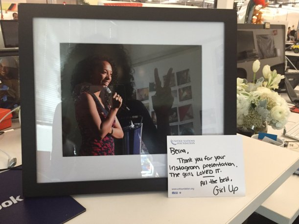 A framed photo of a woman of color speaking onstage.