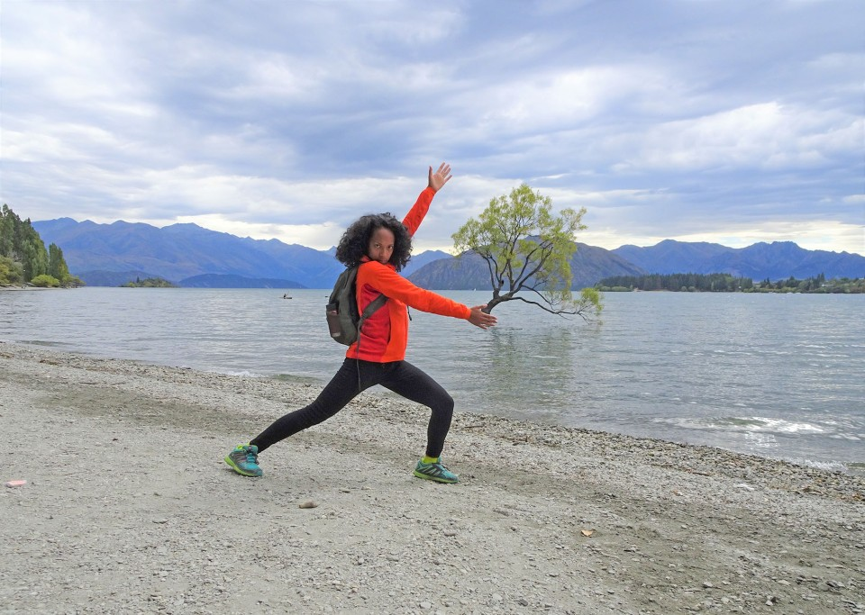 A picture of a brown skinned girl with curly hair in an Arcteryx jacket standing in front of The Wanaka Tree #thatwanakatree in Wanaka, New Zealand.