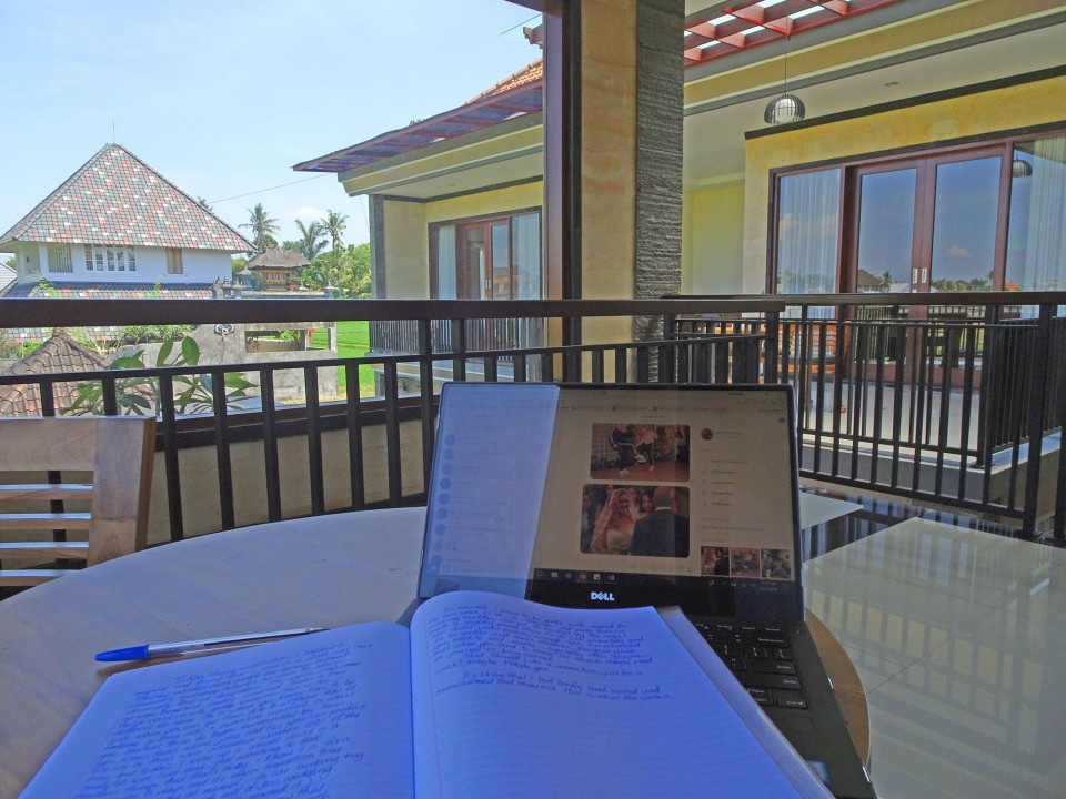 A picture of a laptop and a journal on a table looking out over the rice paddies while working remotely in Ubud as a digital nomad and travel blogger in Bali.