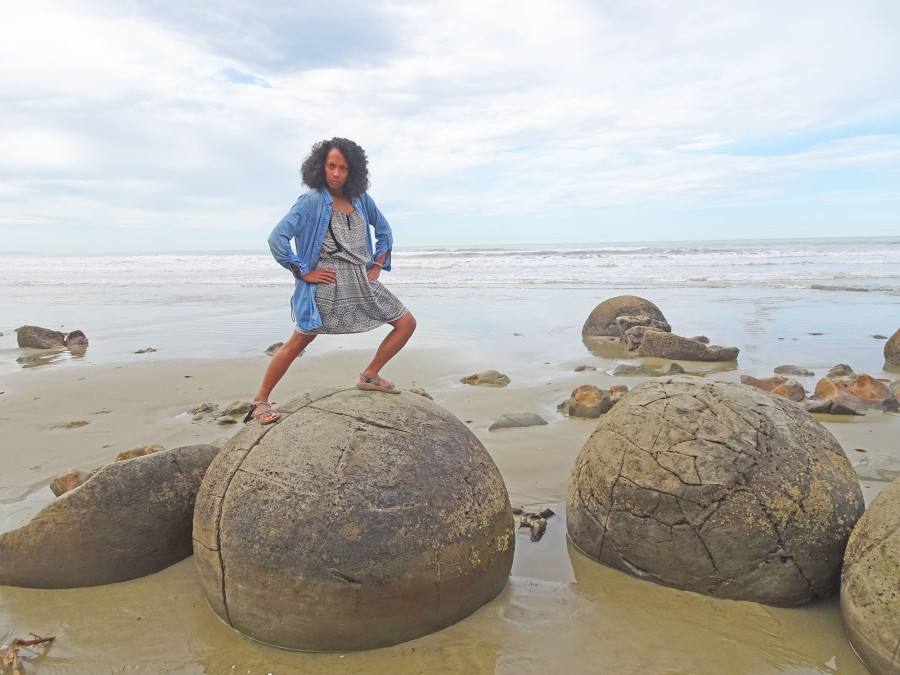A photo of a brown skinned girl with curly hair standing on top of a boulder on a beach at the Moeraki Boulders in New Zealand. She's making a bad metaphor about rocks and when travel gets lonely and difficult. Is it working?