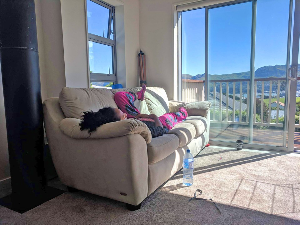 A photo of a brown skinned girl with curly hair laying and resting lazy on a couch in front of a window in Christchurch, while housesitting in New Zealand.
