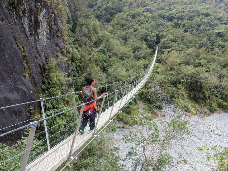 A brown girl with curly hair walking across the Roberts Point Track footbridge near the Franz Josef Glacier in New Zealand, where I thought about what to do when you're homesick and whether my sad ass is showing homesickness symptoms.